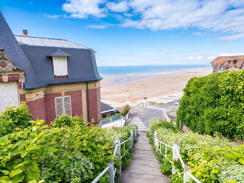 Un petit sentier fleuri relie les maisons à la mer à Deauville en Normandie, une destination idéal pour des vacances d'été en France