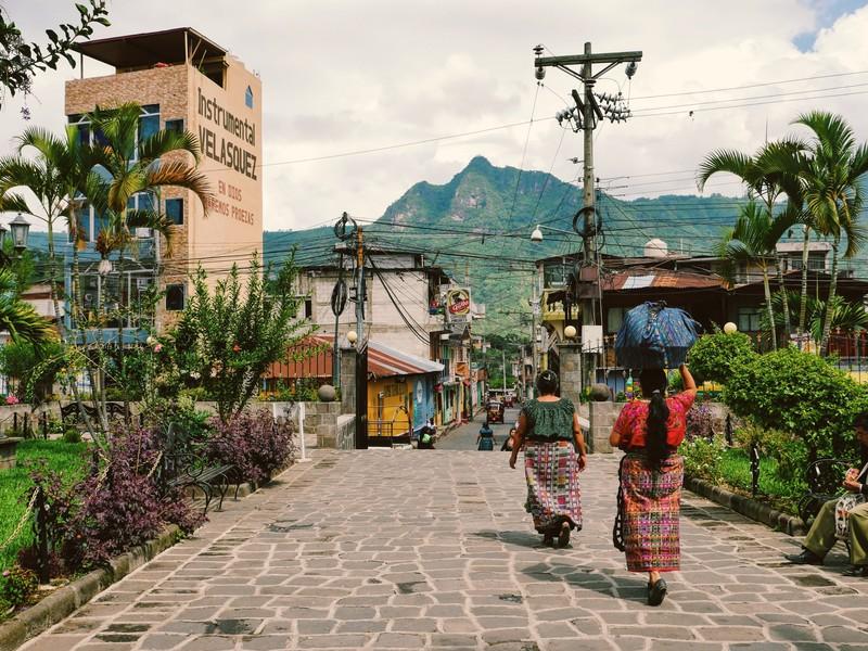 Deux femmes se baladent dans une rue au Guatemala et on aperçoit les montagnes volcaniques en arrière-plan