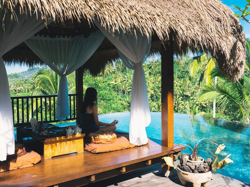 Une femme médite sur une terrase ombragée à Bali au bord d'une piscine à débordement