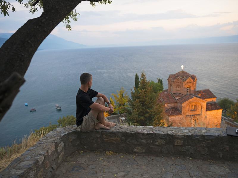 un homme contemple le lac d'Ohrid en Macédoine au bord duquel se trouve une belle église ancienne