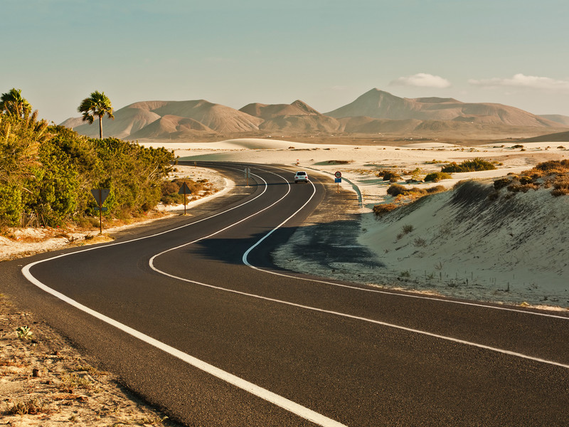Une route déserte sinue à travers les montagnes de sable de Fuerteventura
