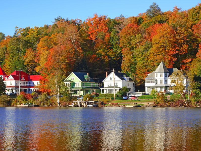 De belles maisons au bord d'un lac avec la forêt en arrière-plan qui commence à rougir et revêtir ses couleurs d'automne dans les Adirondacks au États-Unis